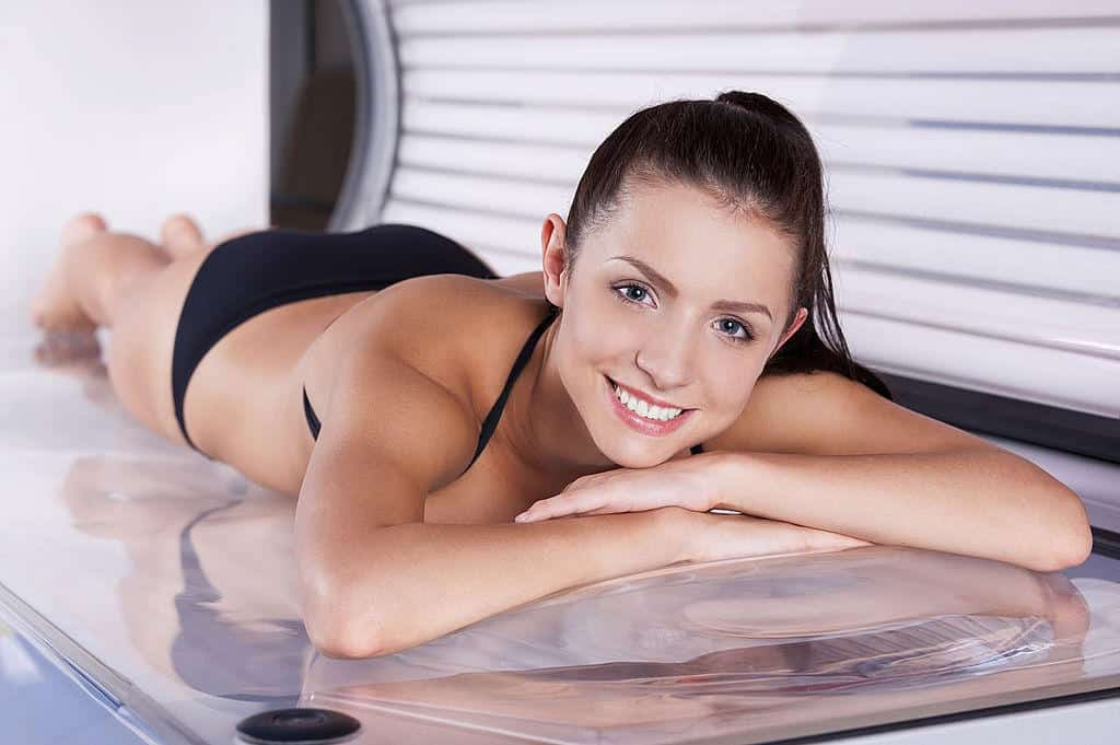 young woman tanning in solarium